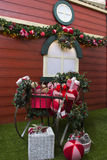 Regalos de la Navidad dentro del trineo, con las flores y el árbol adornado Imágenes de archivo libres de regalías