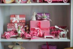 Regalos de la Navidad en caja en un estante, un coche rosado, un aeroplano, un caballo de madera y una campana del gingle Fotografía de archivo libre de regalías