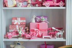 Regalos de la Navidad en caja en un estante, un coche rosado, un aeroplano, un caballo de madera y una campana del gingle Fotografía de archivo