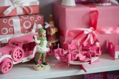 Regalos de la Navidad en caja en un estante, un coche rosado, un aeroplano, un caballo de madera y una campana del gingle Foto de archivo libre de regalías
