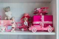 Regalos de la Navidad en caja en un estante, un coche rosado, un aeroplano, un caballo de madera y una campana del gingle Fotos de archivo