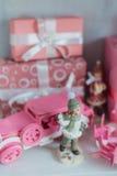 Regalos de la Navidad en caja en un estante, un coche rosado, un aeroplano, un caballo de madera y una campana del gingle Imagen de archivo libre de regalías
