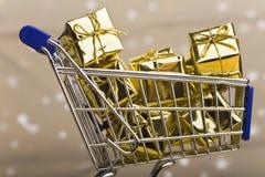 Regalos de la Navidad en carro de compras Imágenes de archivo libres de regalías