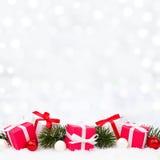 Regalos de la Navidad en nieve con las ramas y el fondo del centelleo imagenes de archivo
