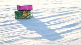 Regalos de la Navidad en un campo en nieve en un tiempo soleado, escarchado y claro al aire libre Foto de archivo