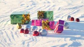 Regalos de la Navidad en un campo en nieve en un tiempo soleado, escarchado y claro al aire libre Fotografía de archivo
