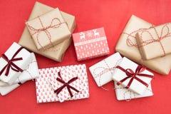 Regalos de la Navidad envueltos en documento del ornamento y cinta decorativa de la cuerda roja sobre superficie roja Afición cre Imagen de archivo