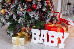 Regalos de la Navidad envueltos en el papel rojo clásico y el BEBÉ de madera de las letras, fondo con el árbol de navidad Copie e fotografía de archivo