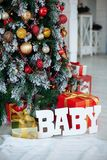 Regalos de la Navidad envueltos en el papel rojo clásico y el BEBÉ de madera de las letras, fondo con el árbol de navidad Copie e fotos de archivo libres de regalías