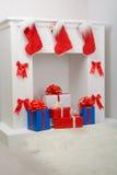 Regalos de la Navidad por la chimenea Foto de archivo