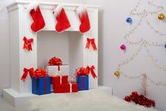 Regalos de la Navidad por la chimenea y el abeto Fotografía de archivo libre de regalías