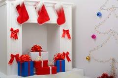 Regalos de la Navidad por la chimenea y el abeto Fotos de archivo