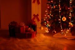 Regalos de la Navidad por la chimenea y el abeto Fotografía de archivo