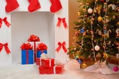 Regalos de la Navidad por la chimenea y el abeto Foto de archivo
