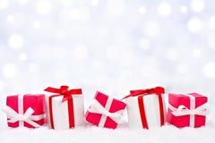 Regalos de la Navidad roja y blanca en nieve con el fondo del centelleo imágenes de archivo libres de regalías