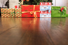 Regalos de la Navidad y del Año Nuevo debajo del árbol en el piso de madera Fotos de archivo libres de regalías
