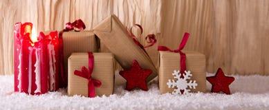 Regalos de la Navidad y vela roja del advenimiento Foto de archivo