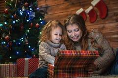 Regalos de Navidad abiertos de la mamá y de la hija Foto de archivo