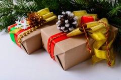 Regalos de Navidad adornados con los conos nevosos y de oro del pino Foto de archivo libre de regalías