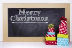 Regalos de Navidad agrupados alrededor de una pizarra Imagenes de archivo