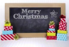 Regalos de Navidad agrupados alrededor de una pizarra Imágenes de archivo libres de regalías