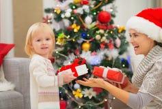 Regalos de Navidad cambiantes de la madre y del bebé Fotografía de archivo libre de regalías