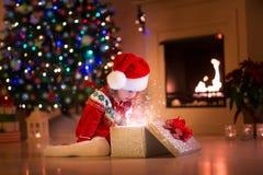 Regalos de Navidad de la abertura de la niña al lado de un lugar del fuego Foto de archivo libre de regalías
