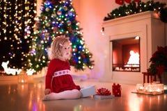 Regalos de Navidad de la abertura de la niña en el lugar del fuego Imagen de archivo libre de regalías