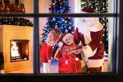 Regalos de Navidad de la abertura de los niños y de Papá Noel Fotografía de archivo