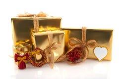 Regalos de Navidad de oro con los ornamentos rojos Fotos de archivo