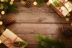 Regalos de Navidad en la caja de Kraft en la tabla de madera del vintage con las decoraciones Fotos de archivo libres de regalías
