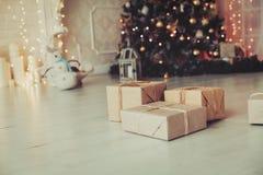 Regalos de Navidad en sala de estar debajo del árbol del Año Nuevo Imagen de archivo libre de regalías