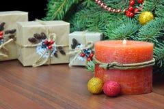 Regalos de Navidad en un estilo rústico y una vela ardiente Foto de archivo libre de regalías