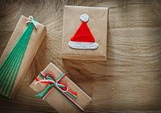 Regalos de Navidad hechos a mano en documento marrón sobre el día de fiesta de madera del tablero fotos de archivo
