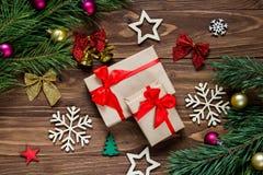 Regalos de Navidad lindos en la tabla de madera rodeada con malla de los Años Nuevos tal como campanas, copos de nieve, estrellas Fotos de archivo libres de regalías