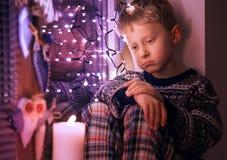 Regalos de Navidad que esperan del niño pequeño triste para Imagenes de archivo