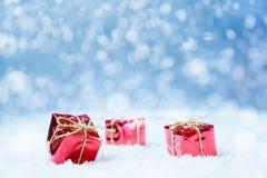 Regalos de Navidad rojos en fondo de la nieve Fotos de archivo