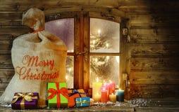Regalos de Navidad y velas en el cristal de ventana Imágenes de archivo libres de regalías