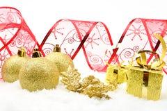 Regalos de oro de la Navidad, cinta roja de las chucherías en nieve Fotografía de archivo libre de regalías