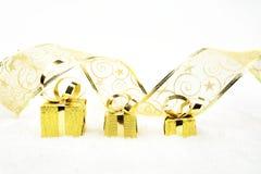 Regalos de oro de la Navidad conforme a cinta en nieve Imagen de archivo libre de regalías