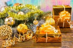 Regalos de oro en la tabla con las decoraciones de la Navidad Imágenes de archivo libres de regalías
