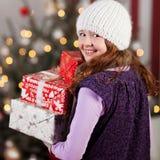 Regalos de risa de la Navidad de la muchacha que llevan Imágenes de archivo libres de regalías