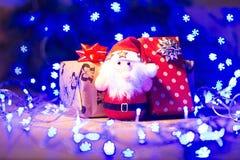 Regalos del Año Nuevo/la Navidad en paquete, el juguete de Papá Noel y la guirnalda azul en la plantilla de madera del fondo Fotografía de archivo libre de regalías