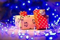 Regalos del Año Nuevo/la Navidad en paquete y guirnalda azul en la plantilla de madera del fondo Imágenes de archivo libres de regalías