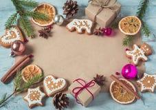 Regalos del fondo, ramas del abeto, conos, galletas de la Navidad y ora Imagen de archivo libre de regalías