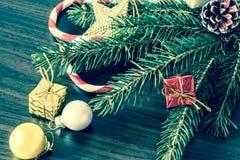 Regalos del ` s del Año Nuevo en una tabla de madera con las velas y un árbol de navidad con los conos Vintage, viejo estilo retr Imágenes de archivo libres de regalías