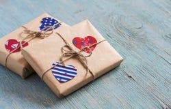 Regalos en el papel de Kraft, corazones de papel del día de tarjeta del día de San Valentín en superficie de madera azul Fotos de archivo libres de regalías