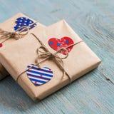 Regalos en el papel de Kraft, corazones de papel del día de tarjeta del día de San Valentín en superficie de madera azul Imágenes de archivo libres de regalías