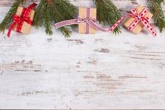 Regalos envueltos con las cintas y ramas spruce verdes para la Navidad o las tarjetas del día de San Valentín Imágenes de archivo libres de regalías