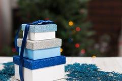 Regalos envueltos en una tabla delante del árbol de navidad Imágenes de archivo libres de regalías